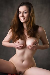Anna-Leah showcases her luscious breasts in the studio with a gray background.